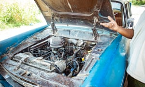 "Alemu Yama looks under the hood of his Peugeot 404. ""A car never dies with quality,"" he says."