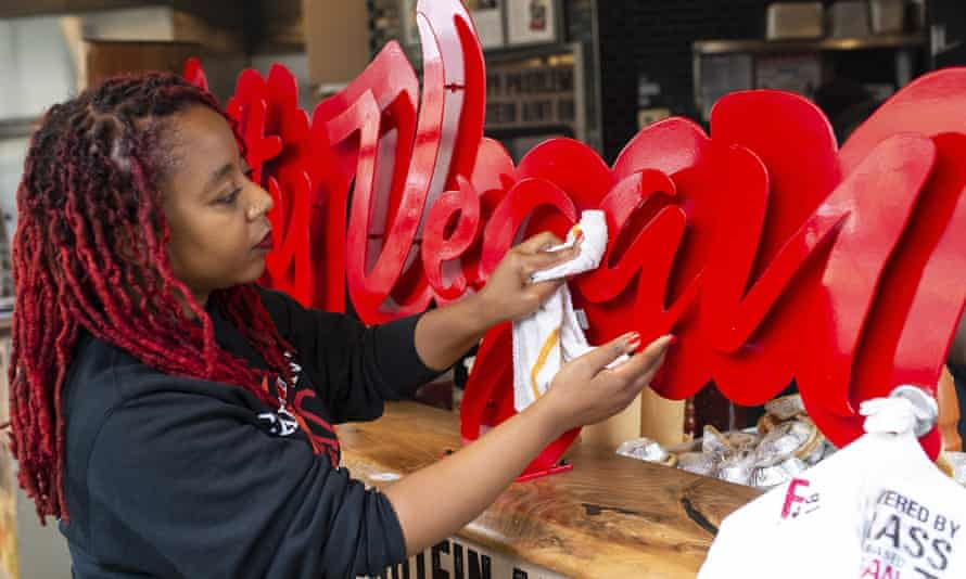 Aisha Pinky Cole, owner of Slutty Vegan restaurants and food trucks, wipes down a sign on her storefront in Atlanta.