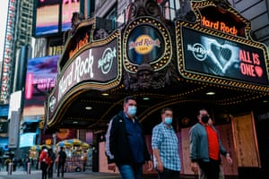Pedestrians wearing face masks walk in front of the Hard Rock Cafe in Times Square, New York, on 10 November.