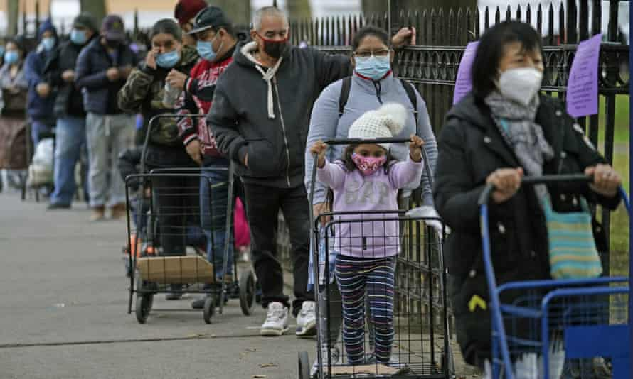 A child rolls a grocery cart as she waits in line to receive donated food in Queens, New York.
