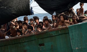 Rohingya migrants sit on a boat drifting in Thai waters