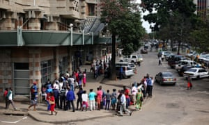 Customers queue to withdraw money at a bank in Harare.