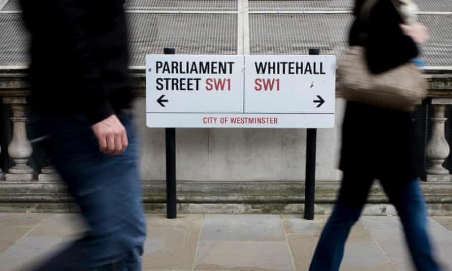 Pedestrians pass a street sign showing Parliament Street and Whitehall
