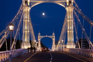 Albert Bridge across the Thames in London, festooned with lights and the moon shining through the night sky behind.