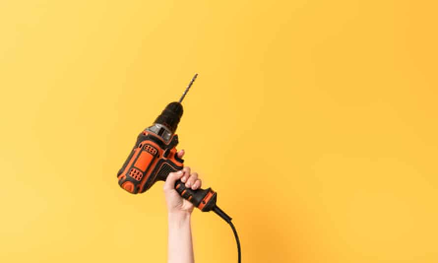 Cropped view of woman holding drill on yellow background