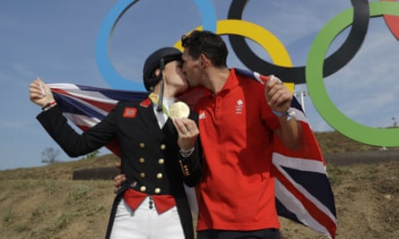 Britain's Charlotte Dujardin, left, poses for with her partner, Dean Golding, after she won a second gold.
