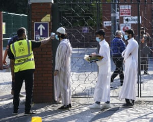 People wearing face masks have their temperatures checked before being allowed to go into Manchester Central Mosque as Muslims worldwide marked the start of Eid.