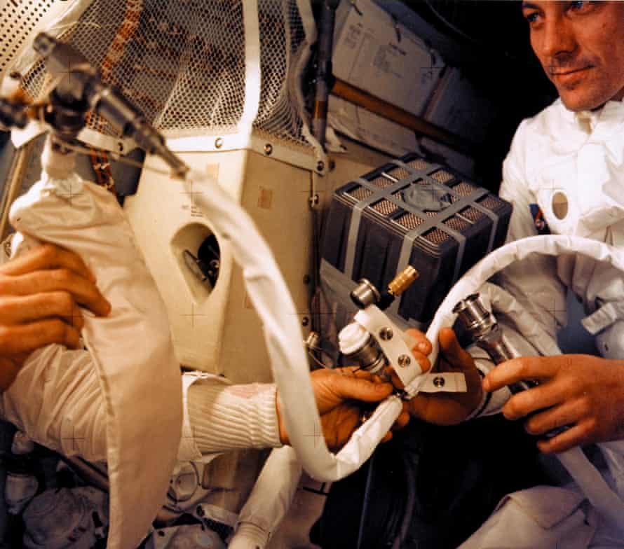jack swigert (right) and one of the other two crew members work an improvised co2 scrubber made from parts found aboard the apollo 13 lunar module