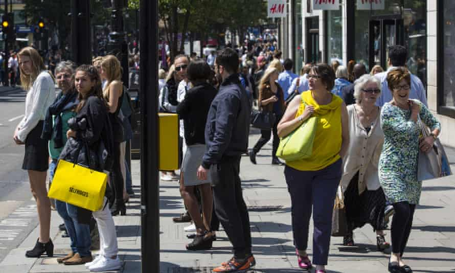 Shoppers wait to cross the road on Oxford Street in London, England