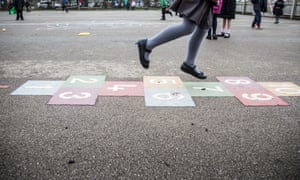 Schoolgirl playing hopscotch in the playground of a primary school