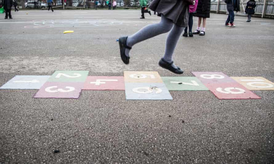 A girl plays hopscotch