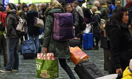 Christmas travellers carrying gifts as they board a train at Euston station in London