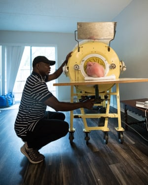 A caregiver adjusts Paul's head rest as he lies in an iron lung in his apartment in Dallas, Texas.