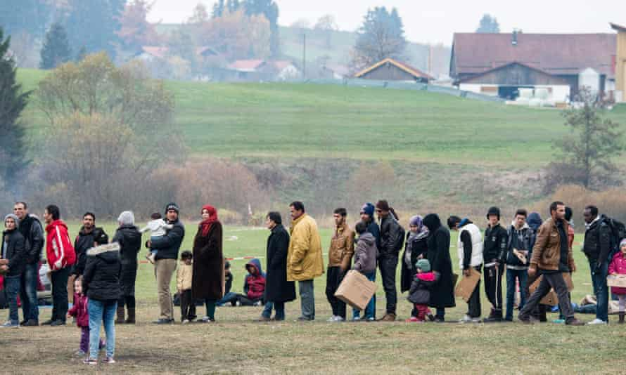 Refugees heading for Germany queue in an Autrian field.