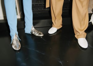 Slim crepe trousers with a V-shape split detail highlight the metallic and white slipper boots.