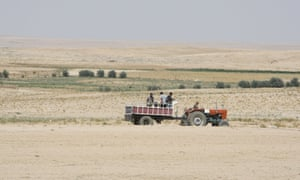 Farmers ride in their tractor in the drought-hit region of Hasaka in north-eastern Syria.