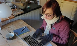 A woman works at home from her cold kitchen