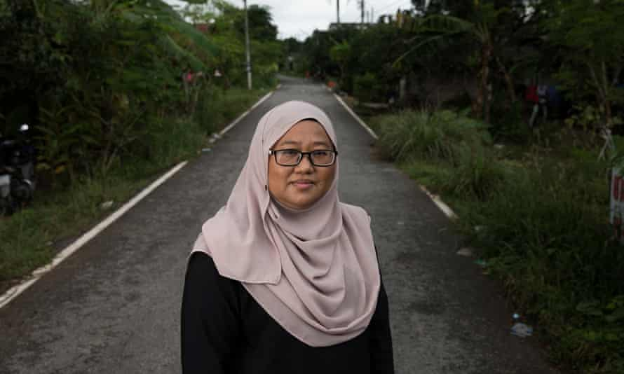 Anchana Heemmina stands on a remote country road in the Pattani countryside after having interviewed the family of an alleged insurgent.