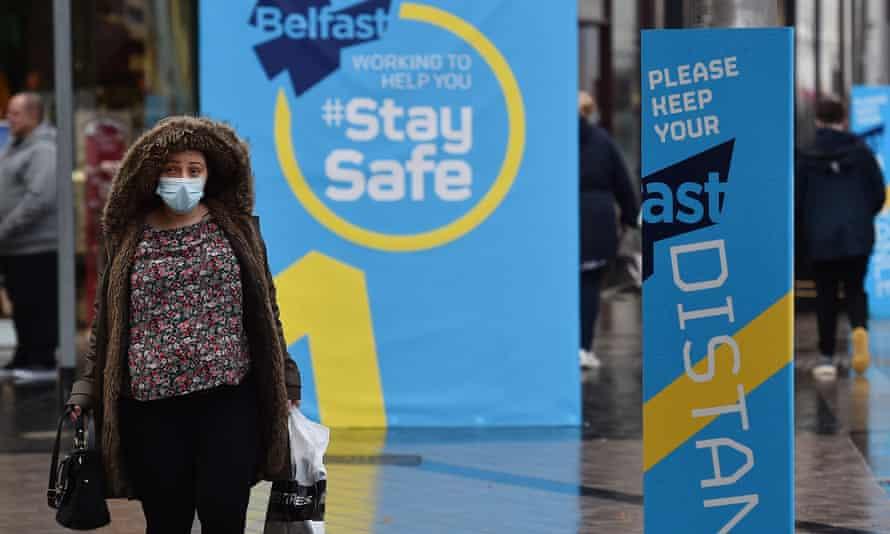 A shopper in Belfast passes public health advice billboards.