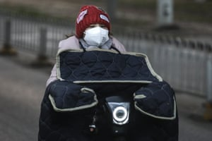 A woman wears a protective mask as she rides on a bicycle
