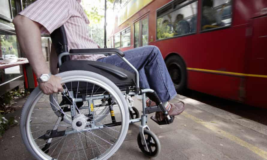 Disabled man in wheelchair at bus stop in London