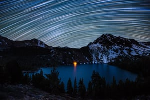 </strong>Star Trails over Green Lake</strong> Star trails illuminate the night sky over a campfire-lit Green Lake in the Hoover Wilderness of California