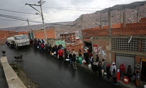 Bolivian citizens stand in line to get water.