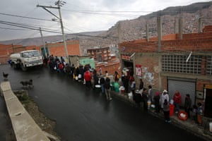 Bolivians stand in line to get water from a truck provided by officials of the Bolivian public water company, Epsas and Bolivian soldiers that distributes water to the neighborhood of areas affected by rationing due to the drought in La Paz