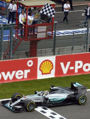 A track marshal waves the flag as Lewis Hamilton crosses the finish line and wins.
