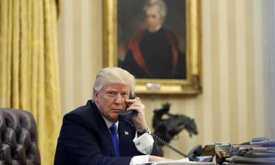 Donald Trump speaks on the telephone in the Oval Office, a portrait of Andrew Jackson behind him.