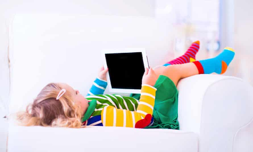 Little toddler girl with tablet pc relaxing on a white couch