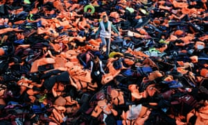 Volunteers walk on a pile of life jackets on the island of Lesbos.