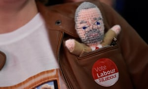 A Labour supporter sports a knitted doll of Jeremy Corbyn at a campaign rally in Leicester.