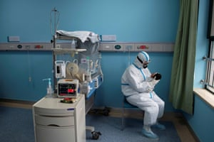 A nurse in a protective suit attends to a baby in an isolation ward at Wuhan Children's Hospital