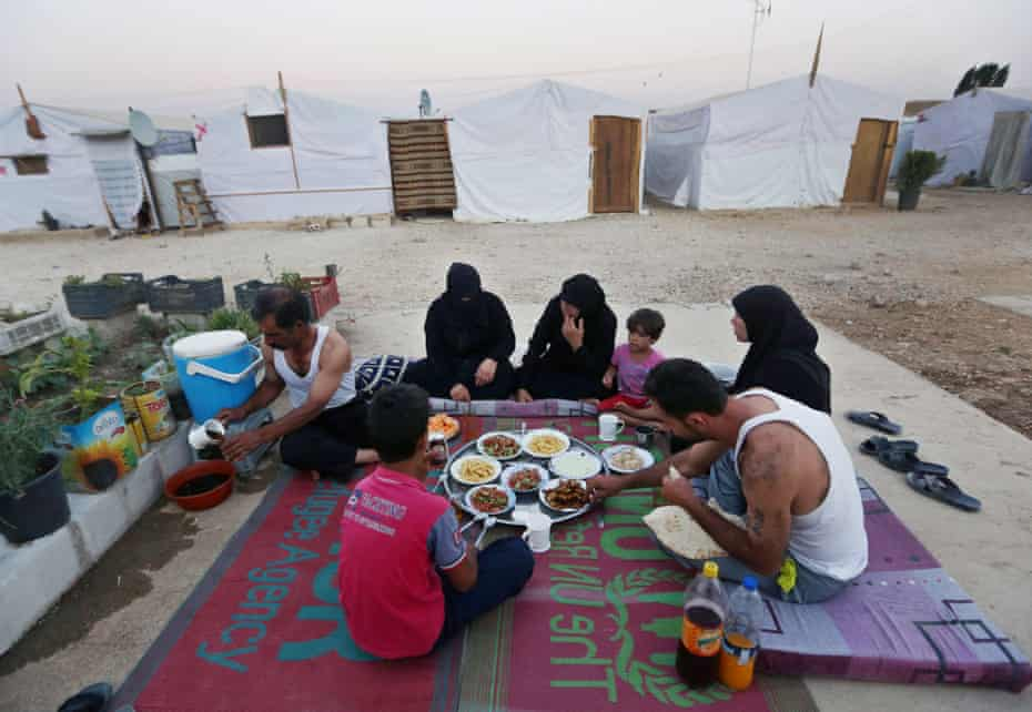 A Syrian family eat a meal outside their tent at a Syrian refugee camp in the Bekaa valley, Lebanon.
