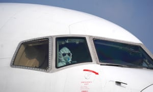 A masked pilot parks an aircraft at the unloading area of Wuhan Tianhe international airport, amid the coronavirus outbreak