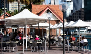 People sitting at a cafe on Sydney harbour.