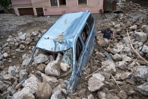 Braunsbach, Germany A woman walks next to a destroyed car among debris left by flooding