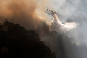A firefighting aircraft attempts to douse the forest fire in Carros near Nice