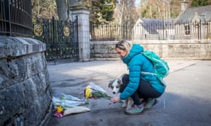 Gayle Cameron, with dog Morlich, lays flowers at the gates of Balmoral Castle in Royal Deeside, Aberdeenshire.