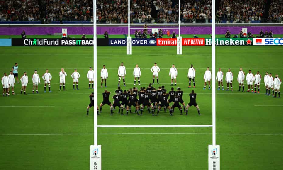 England players look on while New Zealand players perform the haka.