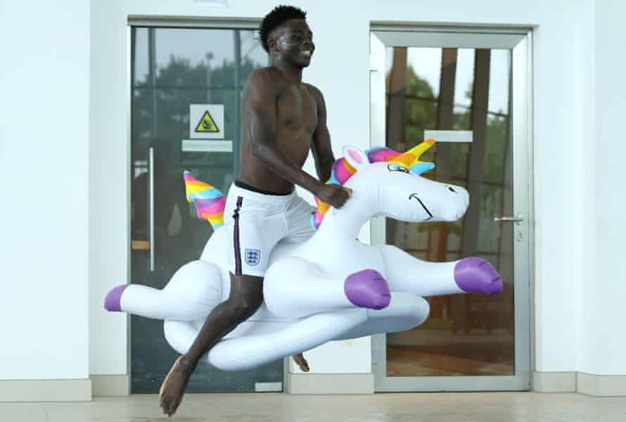 Bukayo Saka of England jumps into the swimming pool on an inflatable unicorn at St George's Park on July 04, 2021 in Burton upon Trent, England