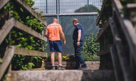An inmate and staff member work in the HMP Parc gardens.