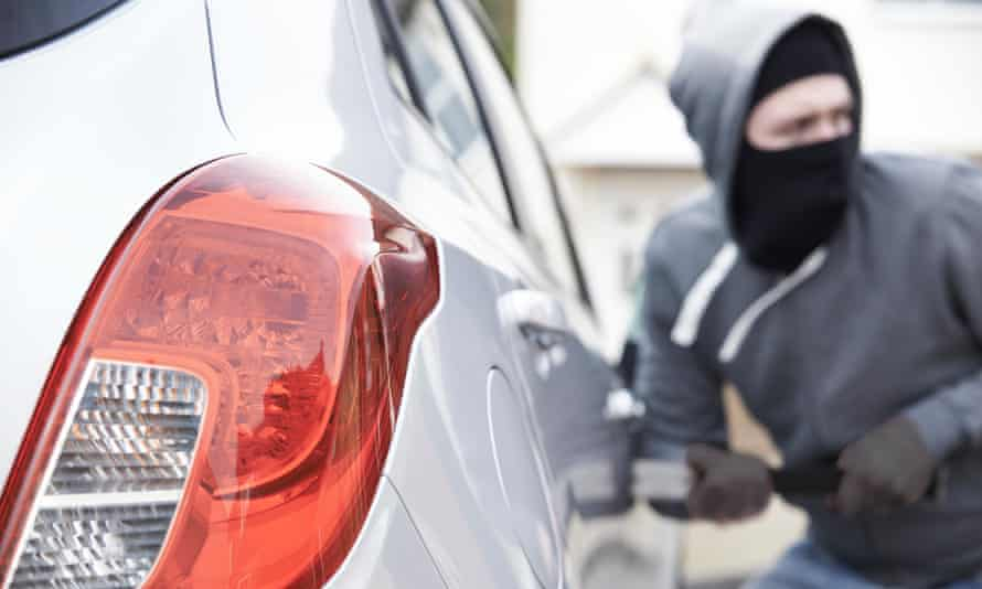 A masked man breaks into a car using a crowbar.