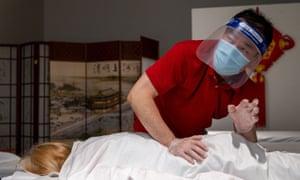 Zhen Wan of YW Massage wears gloves and face masks as he massages a customer in Yuba City.
