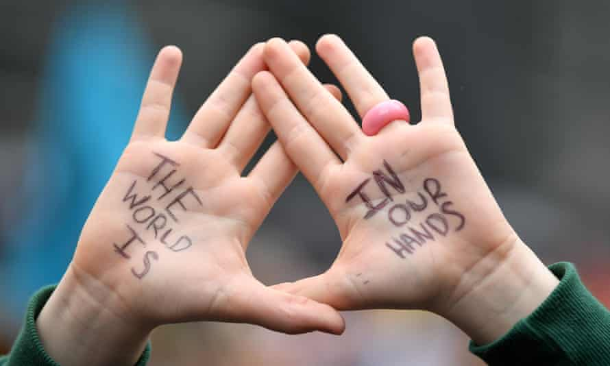 A school student's hold their hands up with the words 'The world is in our hands' written ontheir palms at a School Strike 4 Life protest in Sydney on Friday, May 21, 2021