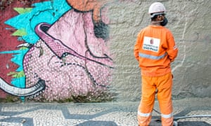 An employee of the Cidade Linda programme paints over street art in São Paulo.