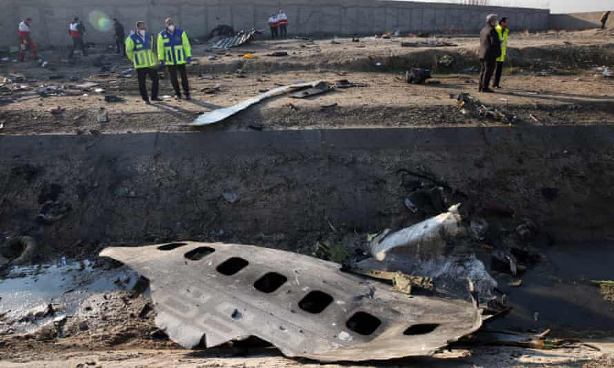 Officials stand near the wreckage of a Ukraine International Airlines Boeing 737-800 after it was shot down in Iran in January 2020. The disaster accounted for more than half of the year's aviation deaths.