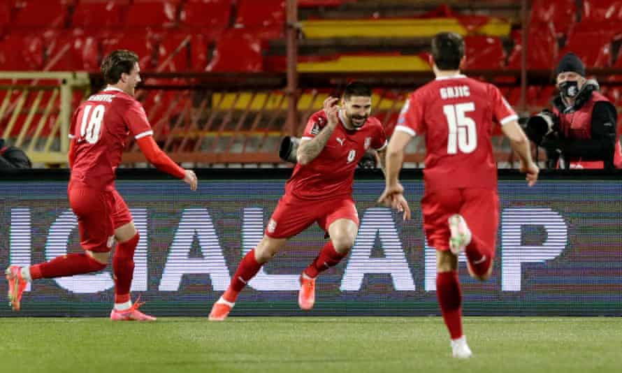 Serbia's Aleksandar Mitrovic celebrates between two teammates rushing towards him after he scored his first goal against Ireland.