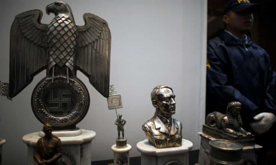 A police officer stands next to Nazi artefacts during a news conference at the Holocaust museum in Buenos Aires. Argentina has a sad history as a bolthole for Nazi war criminals.